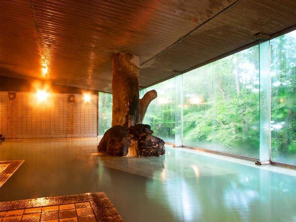 新緑が広がる男性用大浴場。源泉かけ流しの天然温泉です。