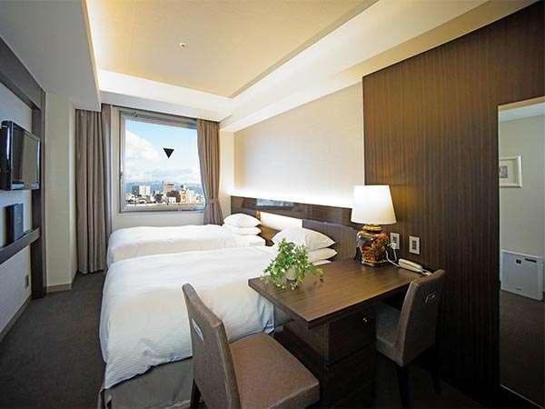 5階以上のスタンダードツインは茶系の家具やじゅうたんでシックにまとめ、高級感のあるお部屋です。