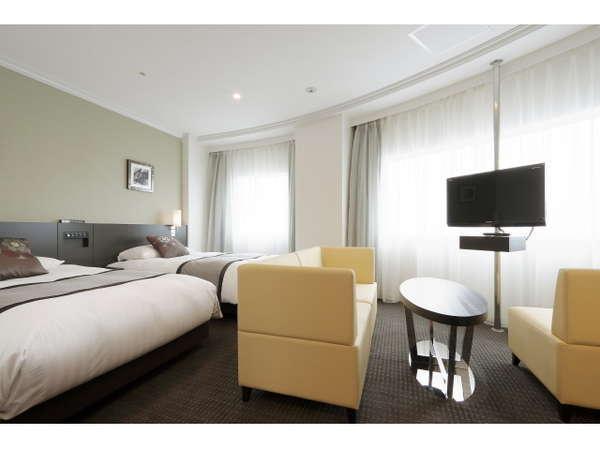 デラックスツインのテレビは回転式。ソファからもベッドからも視聴可能です。