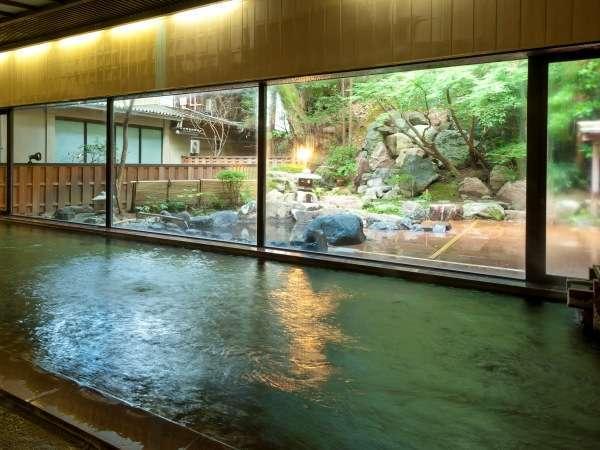 1階の大浴場。ガラスの外には庭園と池に見立てられた源泉かけ流しの露天風呂もございます。