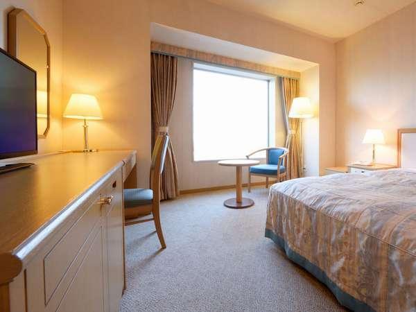 大型の窓とセミダブルサイズのベッドを備えた、ゆったりとしたお部屋です。