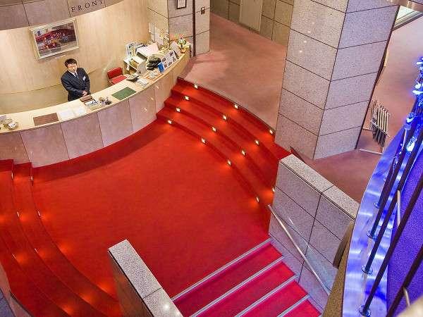 シャンデリアと赤いじゅうたんが印象的な広々としたエントランス