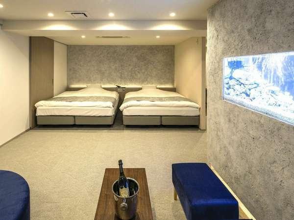 713号室『海』/水槽とサンゴ調の壁面で「海中」気分に。182cm幅ベッドを2台設置。女子旅にもおすすめ。