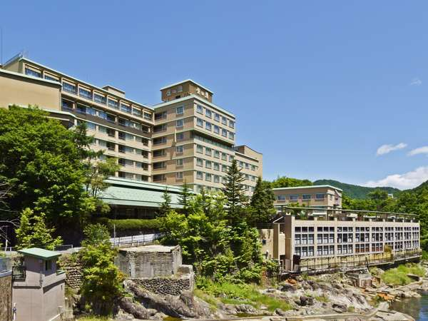 【外観・夏】渓流沿いに建つ、温泉街を象徴する歴史的な建物