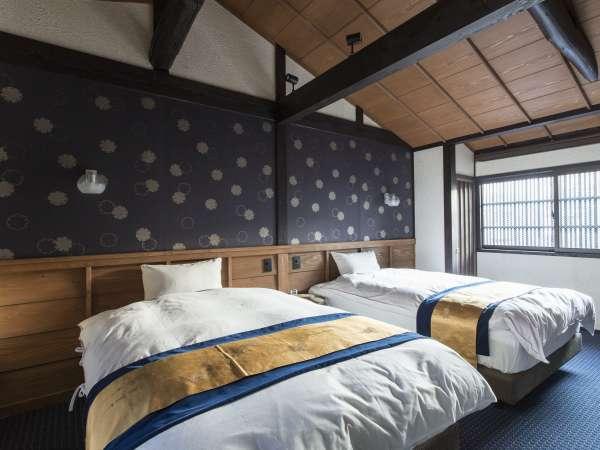 梁の見える高い天井が町家の閉塞感を払拭する蒼黒色が基調の寝室。