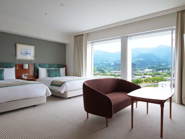 大きな窓から、自然光が優しく照らす室内。シモンズ製クイーンベッドが快適な寛ぎをお約束いたします