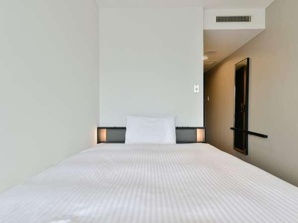 広々としたベッドで旅の疲れを癒してください。