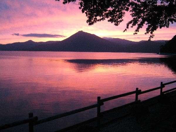 夏の終わりテラスから見る夕焼けに染まる恵庭岳と支笏湖