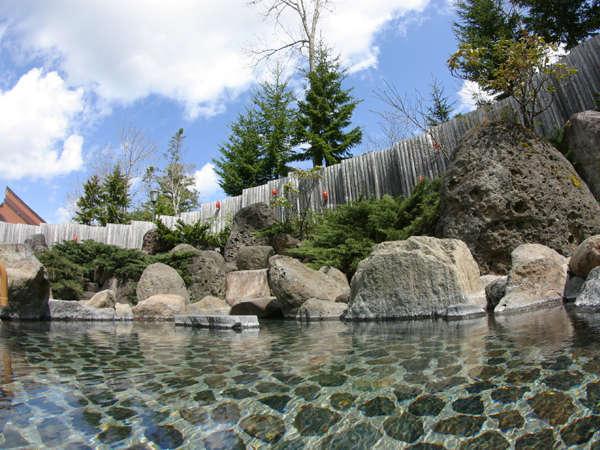 【露天風呂】広々とした露天風呂を、昼間は板垣の上から木々が覗き込み、夜は満天の星空が包み込みます。