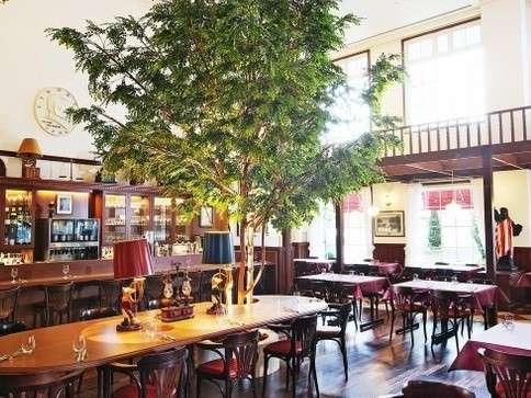 開放感溢れる吹き抜けと樹木が美しいくつろぎのインテリアのレストランリバティ。朝は朝食会場に。