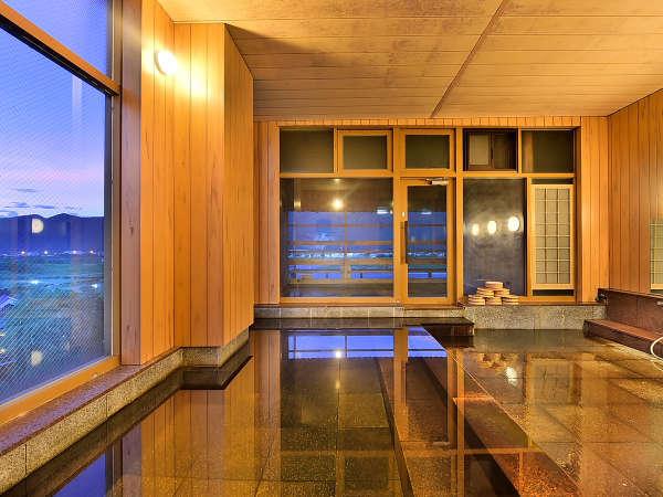 源泉かけ流し!露天風呂へと続く夕暮れの大浴場。サウナもあります(こちらは男湯)。