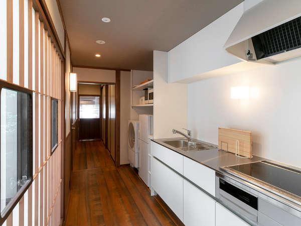 調理器具や食器が備わった共用のキッチンスペース。冷蔵庫や洗濯機もあり、長期の宿泊も安心です。