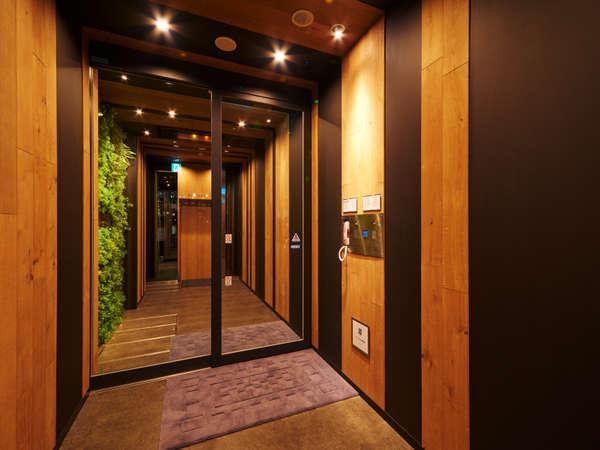 夜のエントランス。奥のエレベーターで2階へお上がり下さい。