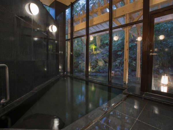 【内湯 夜】窓越しに新緑を楽しめる落ち着いた造りの内湯です。