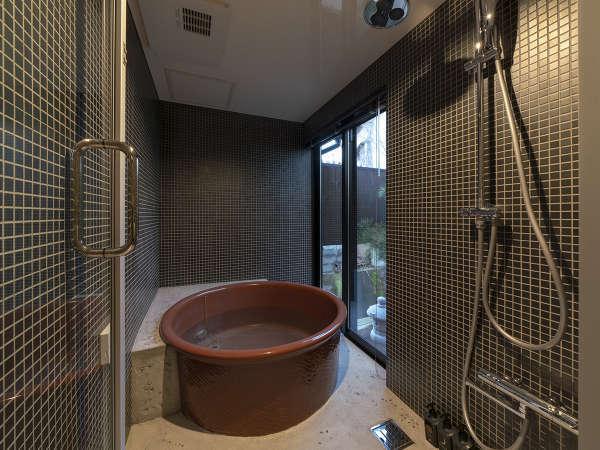 モダンな五右衛門風呂を思わせる浴室。大きな窓からは庭の景色や小川が望め、至福の時間を過ごせます。