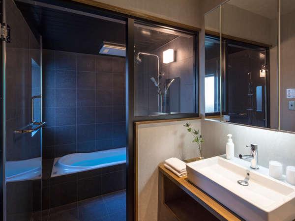 ガラス張りの清潔感ある浴室。石材のタイルが落ち着きをもたせてくれ、安らぎを与えてくれます。