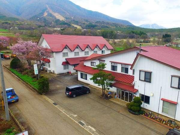 雄大な飯縄山をバックに広がるのどかな田園風景。赤い屋根の大きな建物が目印です。