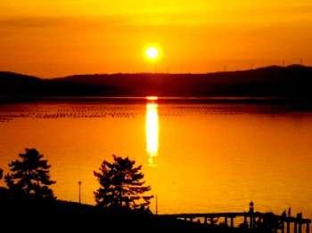 この写真、屋上からワタシが撮りました。ホントですよ。夕日の七尾湾。桟橋には釣り人が3人。