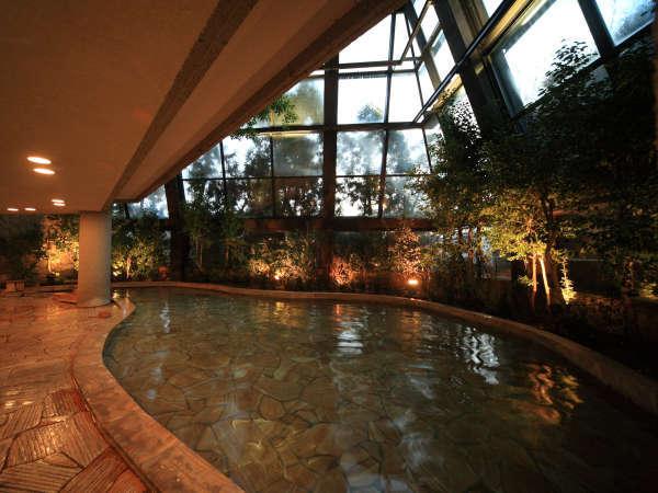 【四季の湯】開放的な吹き抜け、壁面のガラス窓からの景観は夜間照明でさらに幻想的