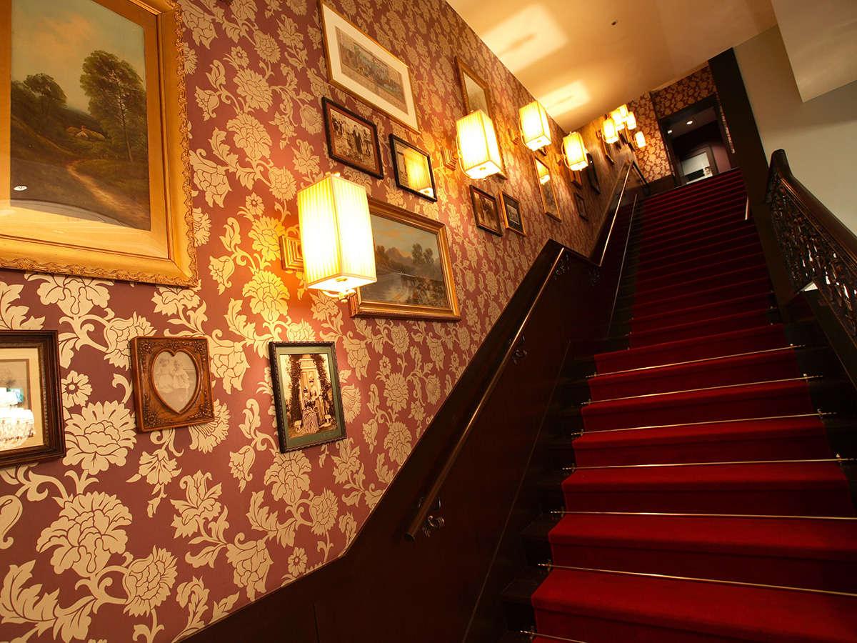 壁面に絵画が飾られ、アンティークな雰囲気漂うホテル内の階段。