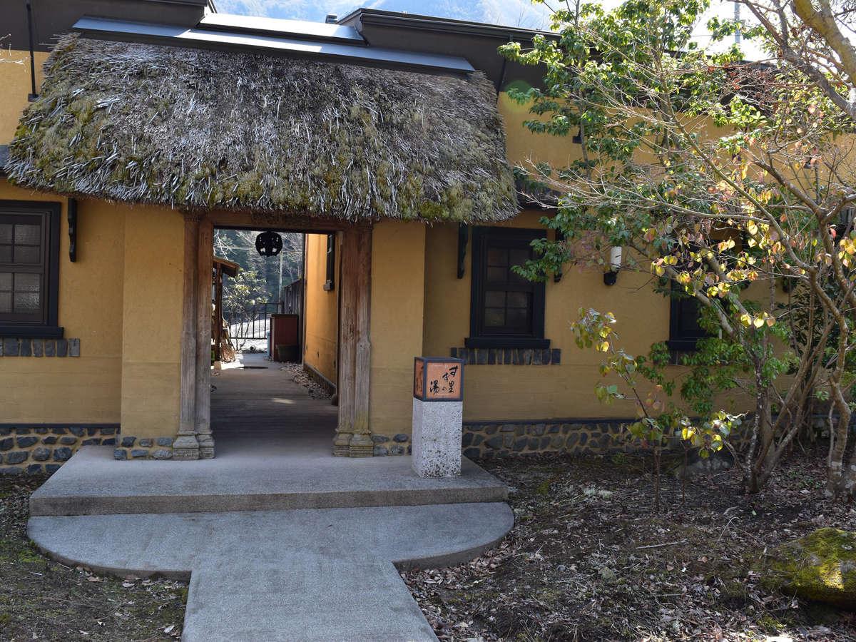 *温泉棟「すず里の湯」入口/緑豊かな山々に囲まれた古民家風の温泉棟は、ほっと心がやすらぐ空間。