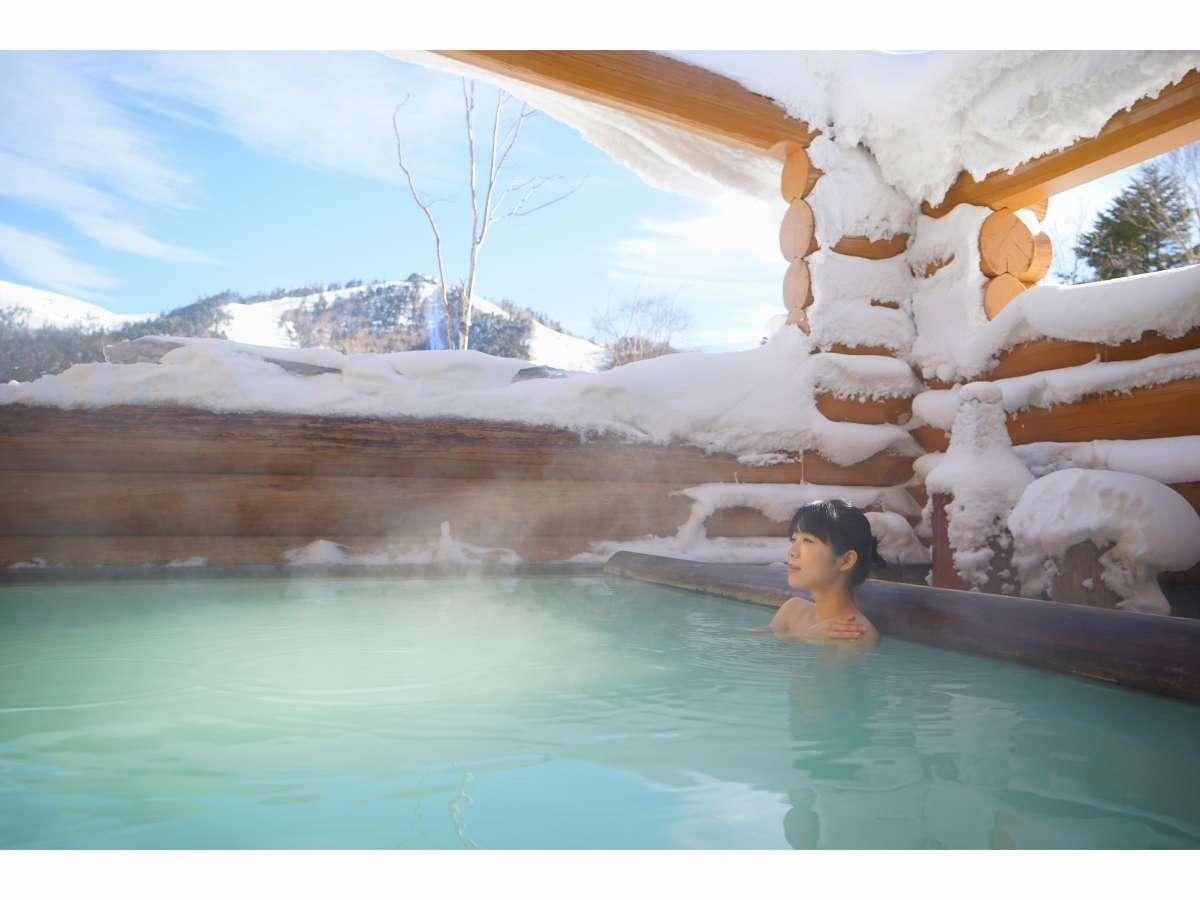 開放的な乳白濁のログ露天風呂