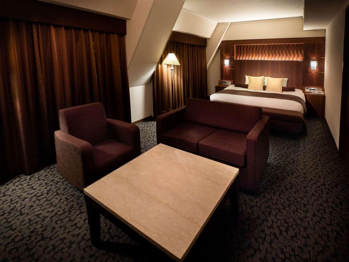 【スイートルーム】存在感のあるキングサイズベッド(200cm幅)の入ったお部屋です。