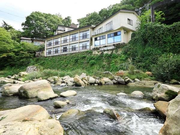 山間に抱かれ、摺上川に面して立つ「おきな旅館」