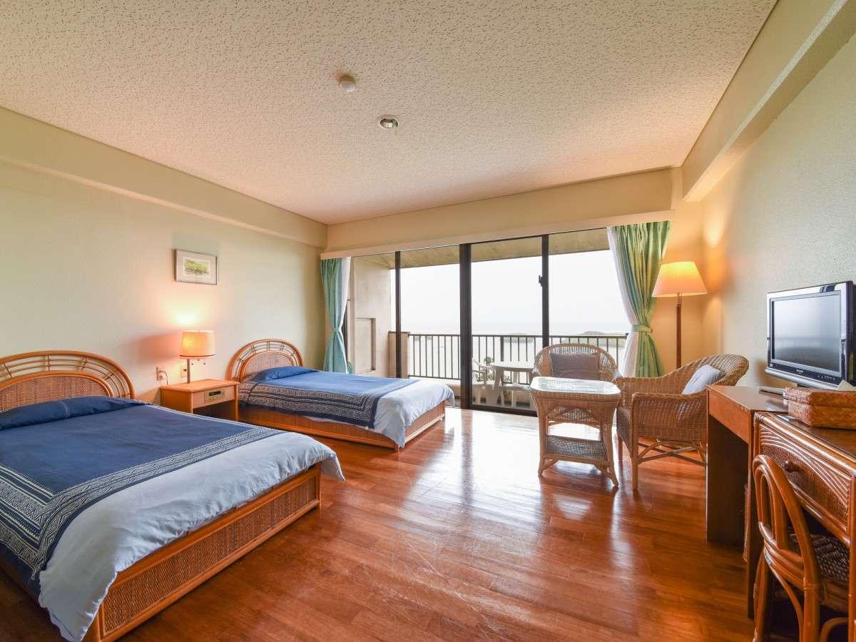 *[洋室ツイン]シングルベッドを配した客室。緑の芝とエメラルドグリーンの海が広がります。
