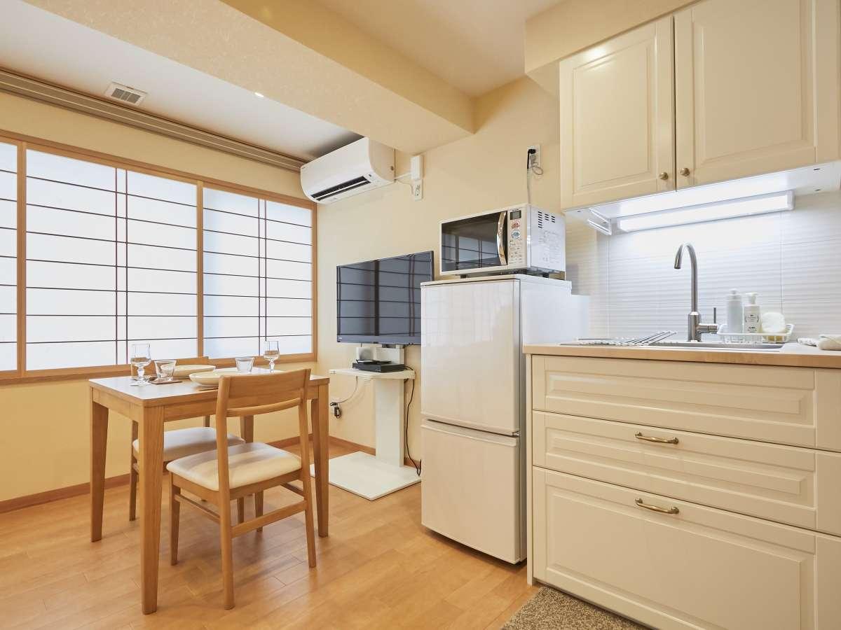 【30平米タイプ】 室内。キッチンとダイニングテーブル。4Kテレビの40型を用意。ブルーレイあり