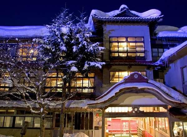 雪景色とも調和し風情ある木造三階建て総けやき造り本館正面玄関。「日本温泉遺産を守る会」認定。