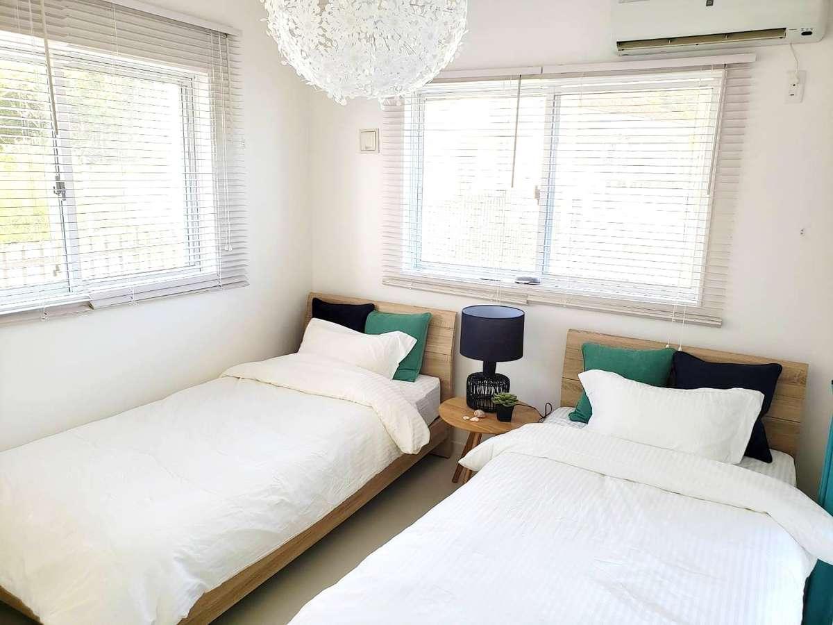 シングルベッドが2台の洋室。太陽の光が緩やかに差し込む、白基調の落ち着いた寝室です。