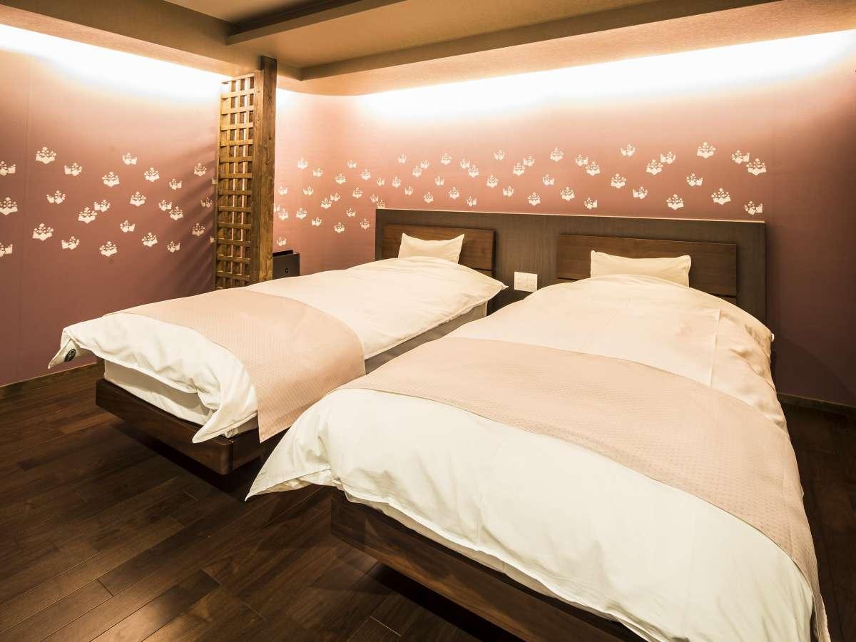 1階ベッド。シーリーのマットレスとこだわりの寝具をご用意。紅梅色の唐紙の壁紙が特徴です。