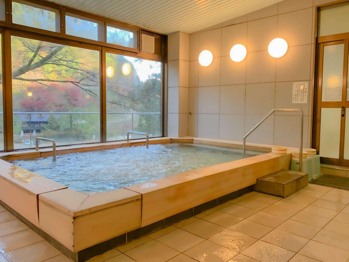 *大浴場1F。お風呂の大きな窓からは勝浦川と緑を眺められます。