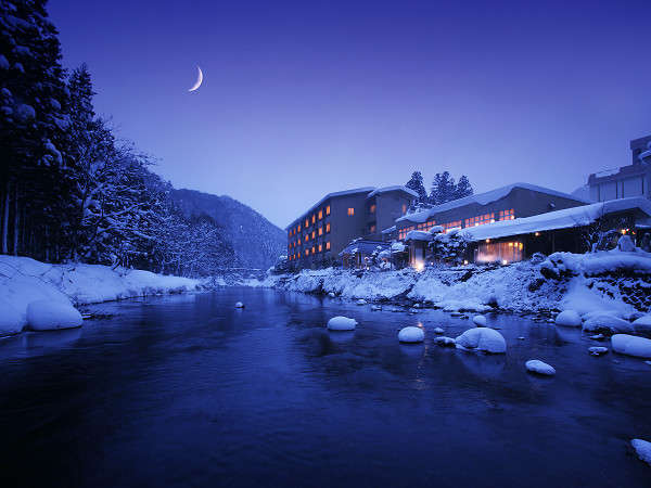 豊沢川から見た夜明けの外観。全てのお部屋は川に面した露天風呂付き客室。雪見風呂はまさに絶景です。