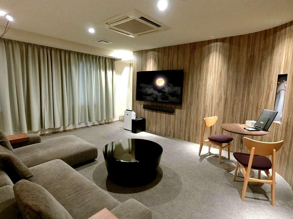 813号室/L字型の大きなソファでのんびり寛ぐことができる。