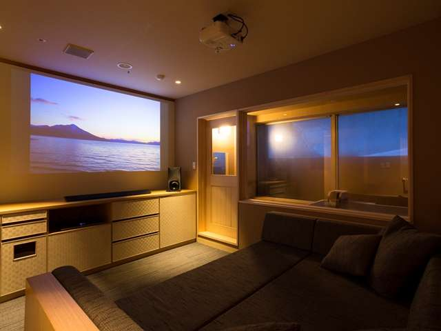 温泉&シアター付客室。ソファ正面の壁にプロジェクターで映像を映します。向かって右奥が温泉内風呂。