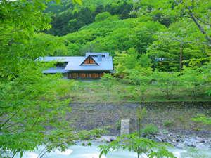 渓谷沿いの鮮やかな緑に包まれる秘湯の宿