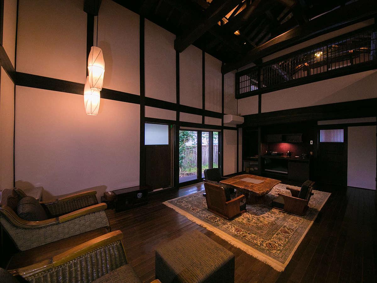 【お部屋一例】1階には板の間にテーブルと肘掛け付の座椅子ソファが置かれ、和風リビングとなっております