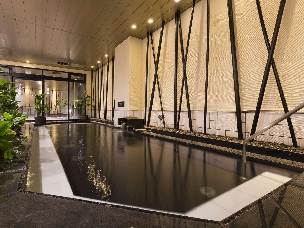 <天然温泉 華楽(かぐら)の湯>蔵の湯内湯 つややかな石造りの浴槽を備えています。