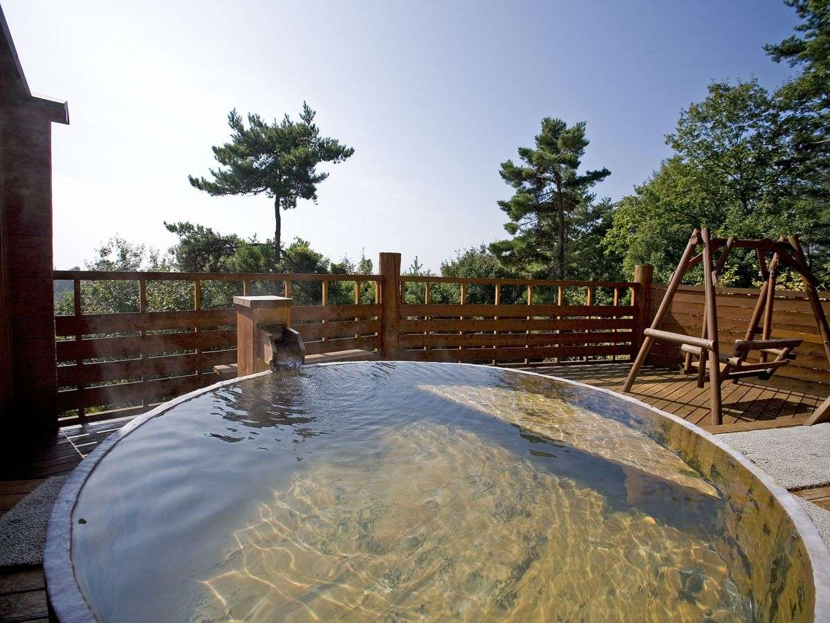 「雲の助」の名物、露天大桶風呂。突き抜ける青空と桶風呂の水面が印象的です。