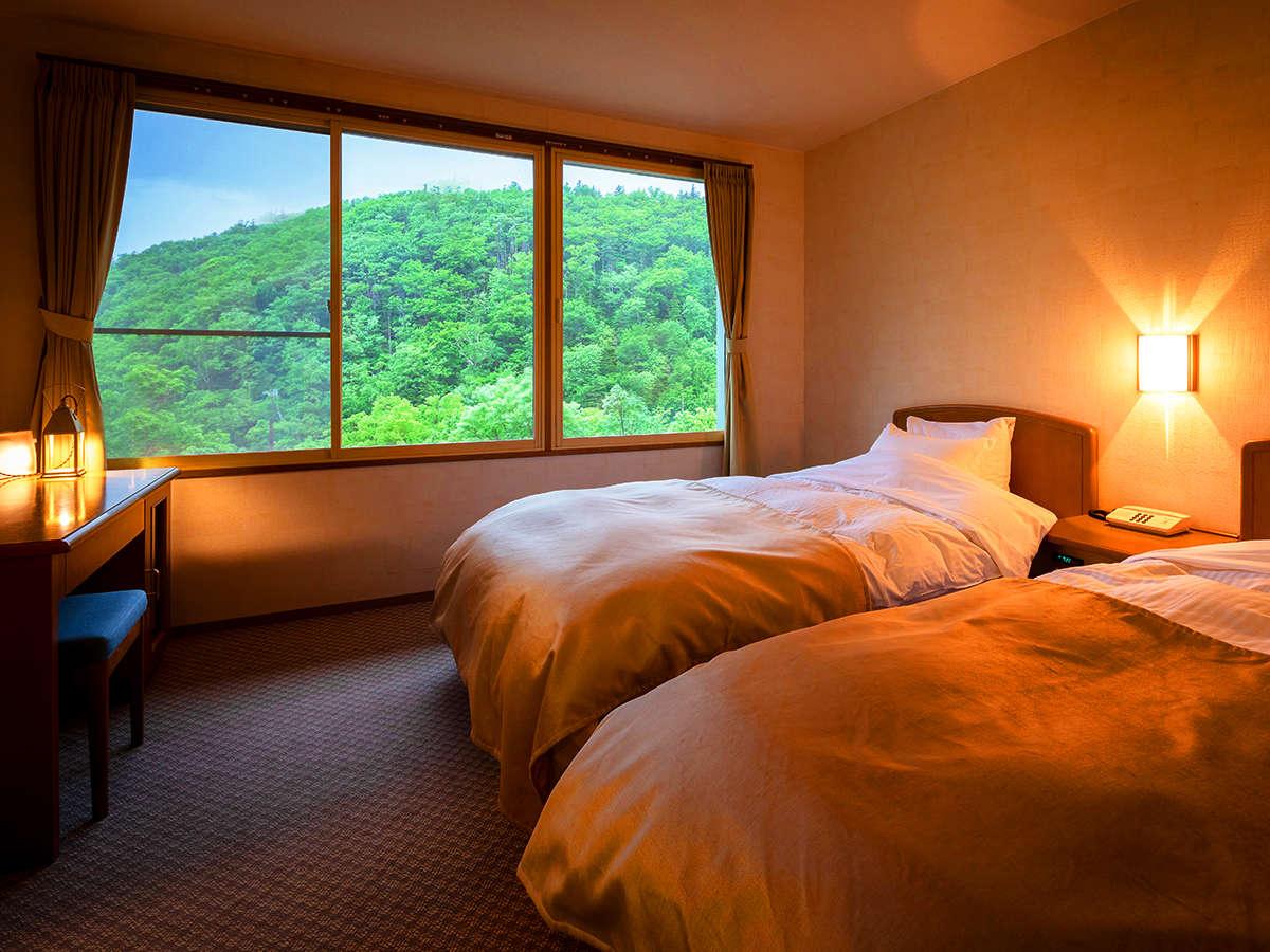お部屋から見える知床の雄大な森。窓を開けると澄んだ空気と共に緑の匂いがお部屋を優しく包み込む