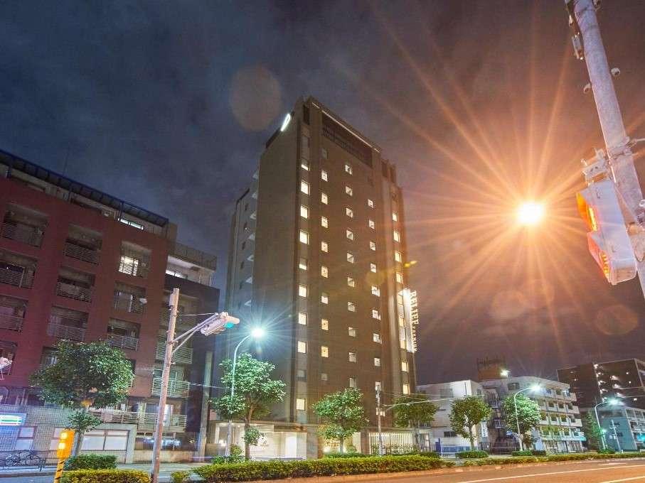 【ホテル外観】コンビニエンスストア横の環八沿い面した茶色い建物です。