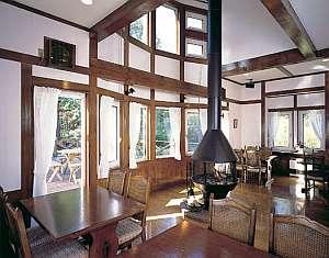 ペンションベルク:暖炉のあるダイニング。窓の外は林とウッドデッキ