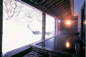 【冬】当館自慢の天然温泉露天風呂。川の流れと雪景色は格別です。