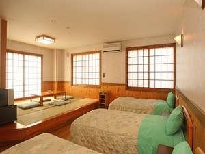 お宿 おばたけ:寛ぎの畳スペースと、ベッドが3台ある和洋室。グループやファミリーに人気