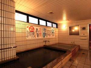 天然温泉大浴場。当館敷地内に湧きだす天然温泉を利用。※床が黒くなっているのは、温泉成分の影響です。