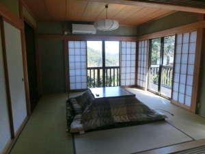 お宿 森のおくりもの:ウッドデッキのある明るい8帖和室です。山の眺望や雑木林の緑も手に届くように眺められます。