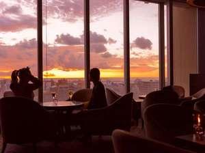 【バーラウンジ】サンセットアワー 変化する那覇の景色と遠く西に沈む太陽