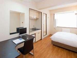 フォーリーブスイン 長居:広めの部屋(約8畳)にセミダブルのベッドと大きな机を備えています。